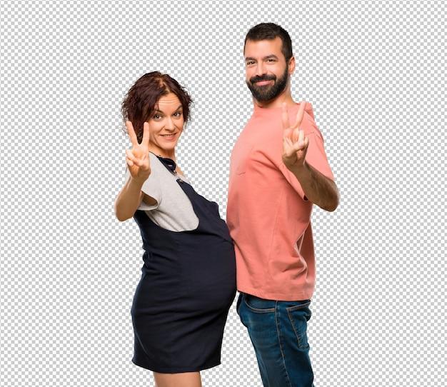 笑顔と勝利のサインを示す妊婦とのカップル