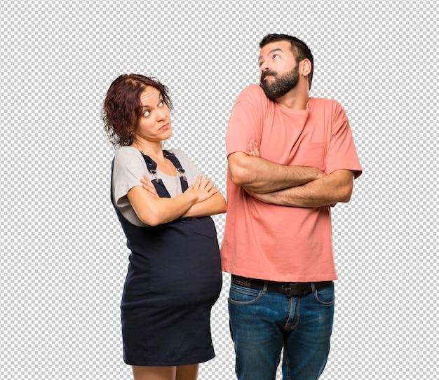肩を持ち上げている間、妊娠中の女性と重要でないジェスチャーをするカップル