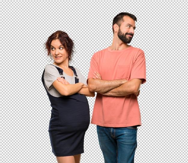 笑顔で肩の上を見ている妊婦とのカップル