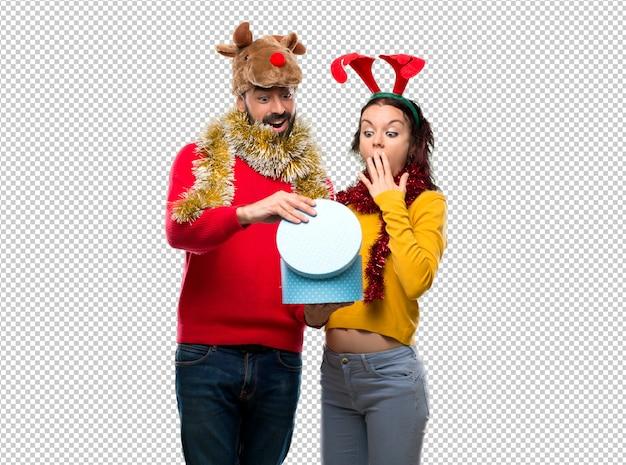 Пара, наряженная на рождественские праздники, держащая подарок