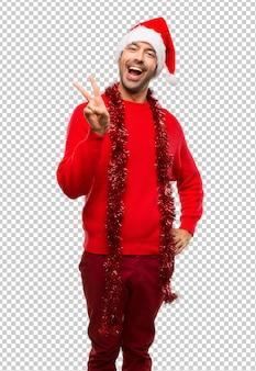 Человек с красной одежды празднует рождественские праздники улыбается и показывает знак победы