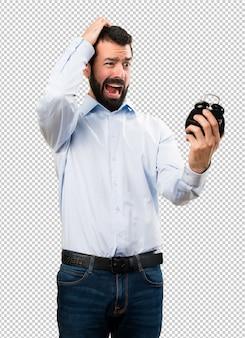 ビンテージの時計を保持しているひげ剃りの男