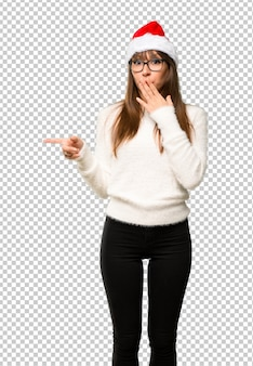 Девушка с празднованием рождественских праздников указывая пальцем в сторону с удивленным лицом