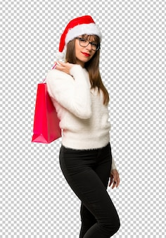 買い物袋をたくさん持っているクリスマスの休日を祝うと少女