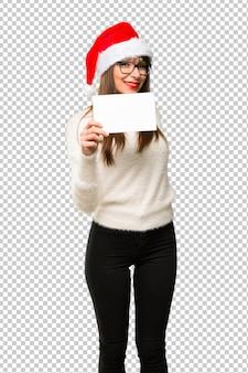 Девушка с празднованием рождественских праздников, проведение пустой белый плакат для вставки концепции