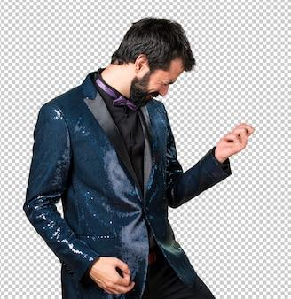 ギターのジェスチャーを作るスパンコールジャケットのハンサムな男