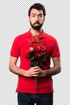 花を抱えている悲しいハンサムな男