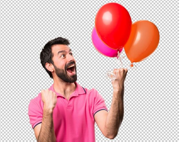 幸運なハンサムな若い男が風船を持っている