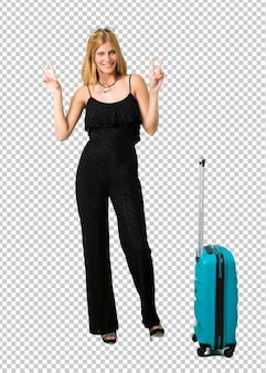 笑みを浮かべて、勝利のサインを示す彼女のスーツケースと一緒に旅行ブロンドの女の子