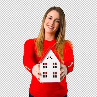 小さな家を持って幸せな若いブロンドの女性