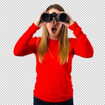 双眼鏡を持つ若いブロンドの女性