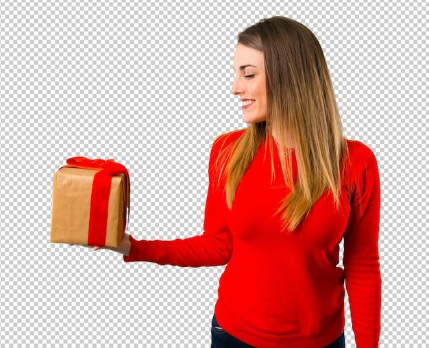 贈り物を持って幸せな若いブロンドの女性