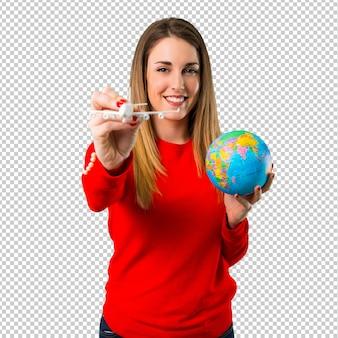 おもちゃの飛行機を持って幸せな若いブロンドの女性