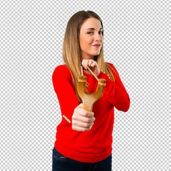 パチンコを持つ若いブロンドの女性