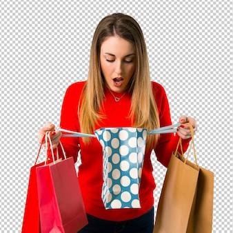 買い物袋を持つ驚く若いブロンドの女性