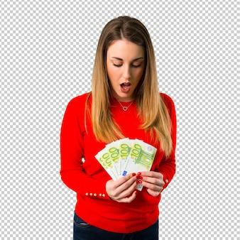 たくさんのお金を取って驚いたの若いブロンドの女性