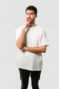 疑いを持っていると見上げながら混乱の表情を持つ白いシャツの若い男
