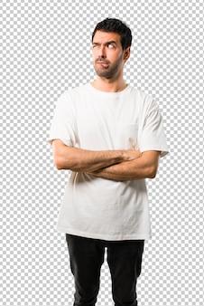 疑問を持っていると混乱の表情を持つ白いシャツを持つ若い男が唇をかみます。