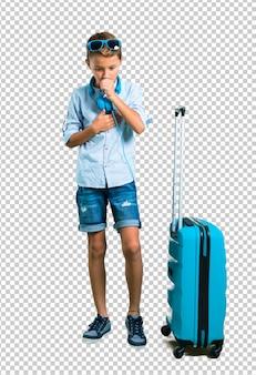 彼のスーツケースと一緒に旅行するサングラスとヘッドフォンを持つ子供は咳で苦しんでいます