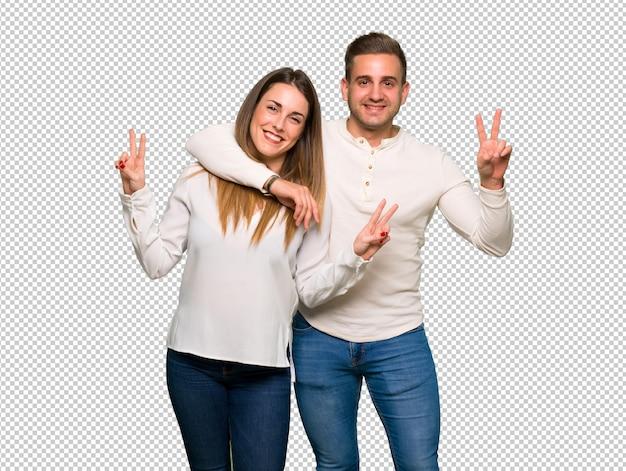 笑顔で勝利のサインを示すバレンタインの日のカップル