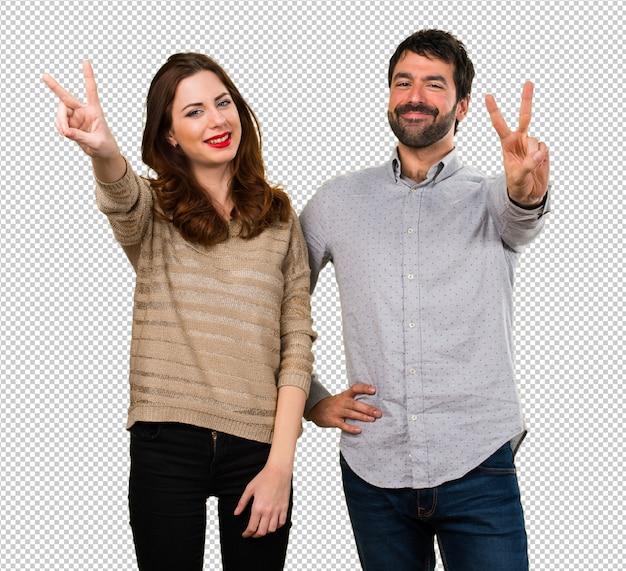 若いカップル作る勝利のジェスチャー