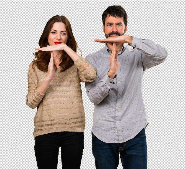 若いカップル作るタイムアウトジェスチャー