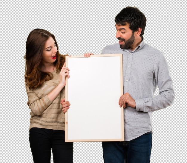 空のプラカードを持っている若いカップル