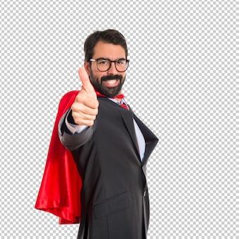 親指でスーパーヒーローのような格好のビジネスマン