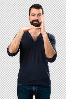 タイムアウトのジェスチャーを作るひげを持つハンサムな男