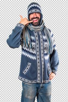 電話のジェスチャーを作る冬服を持つ男