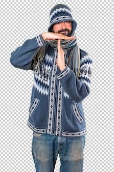 タイムアウトのジェスチャーを作る冬服を持つ男