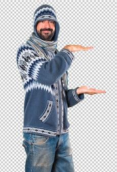 何かを保持している冬服を持つ男