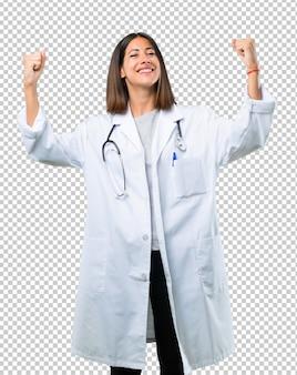 Доктор женщина с стетоскоп, празднует победу в положении победителя