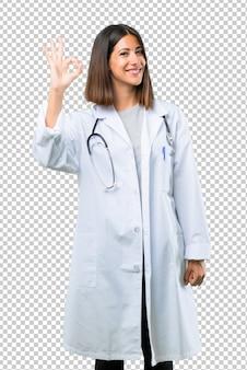 Женщина доктора при стетоскоп показывая одобренный знак с пальцами. лицо счастья и удовлетворения