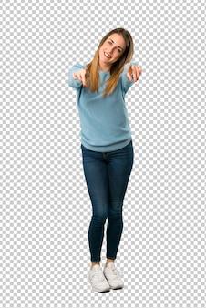 青いシャツを着た金髪の女性が笑顔ながらあなたに指を指す