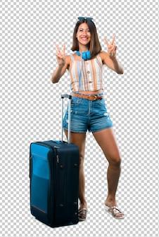 笑みを浮かべて、両手で勝利のサインを示す彼女のスーツケースと一緒に旅行の女の子