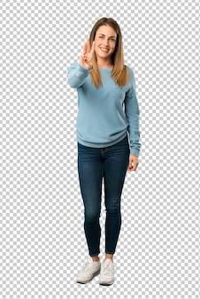 Белокурая женщина в синей рубашке счастлива и считает три пальца