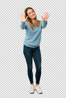 Блондинка в голубой рубашке, считая десять с пальцами