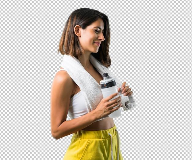 ボトルとタオルを持つスポーツ女性