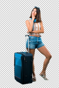 Девушка путешествуя с ее чемоданом стоя и думая идея пока смотрящ вверх