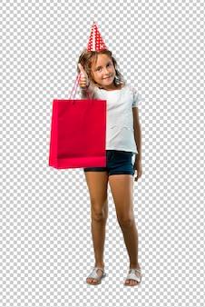 ジェスチャーを親指をあきらめると笑みを浮かべてギフト袋を保持している誕生日パーティーで小さな女の子