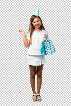 笑みを浮かべて、勝利のサインを示すギフトバッグを持って誕生日パーティーで小さな女の子