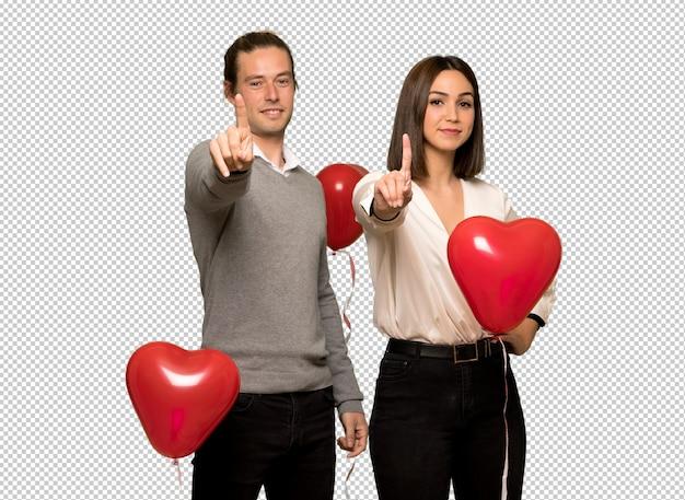 バレンタインの日を示すと指を持ち上げるのカップル