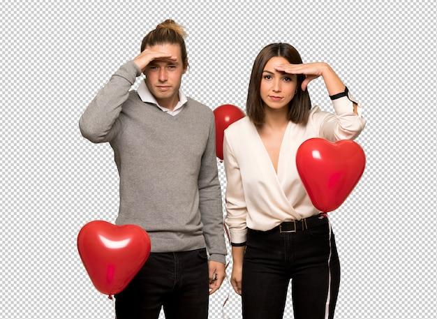Пара в день святого валентина смотрит далеко с рукой, чтобы посмотреть что-то
