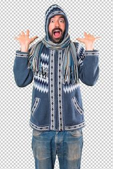 驚きのジェスチャーを作る冬服を持つ男
