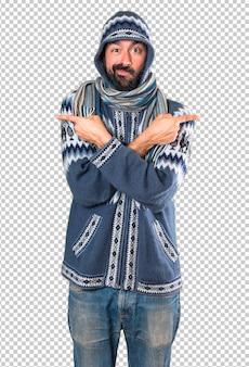 疑問を抱いて外側を指している冬の服を持つ男