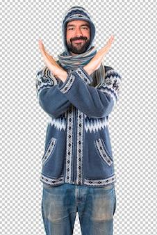 ジェスチャーを作る冬服を持つ男