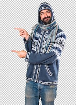 側面を指している冬の服を持つ男