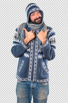 親指で冬服を持つ男
