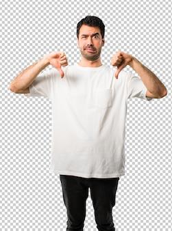Молодой человек с белой рубашкой, показывая большой палец вниз обеими руками. негативное выражение